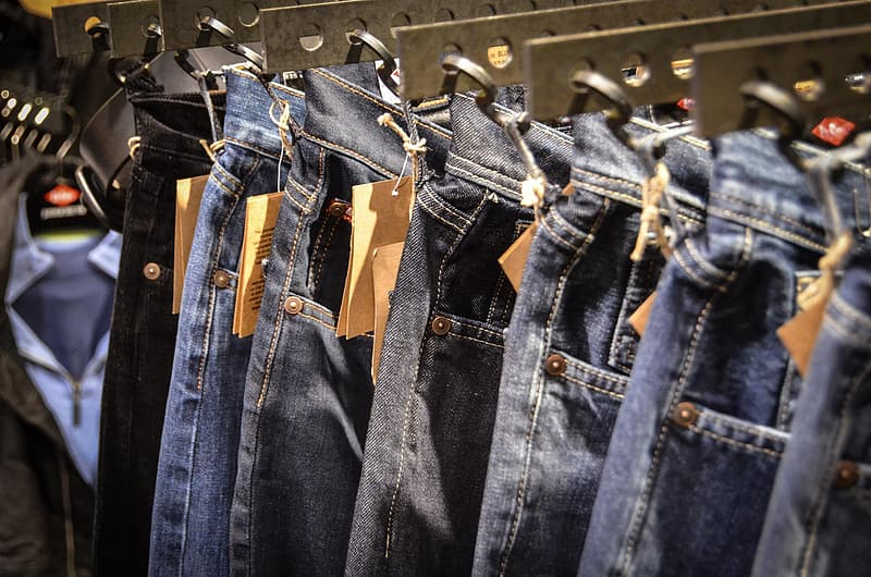 Blue denim jeans hanged on clothes hanger