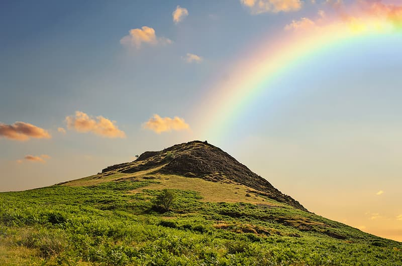 Green and brown mountain with rainbow at daytime