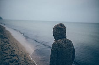 Person in gray hoodie standing on seashore during daytime