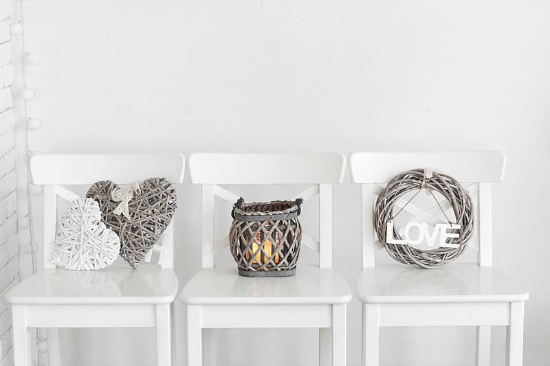 Gray wicker wreath and candle holder on top of three white wooden chairs