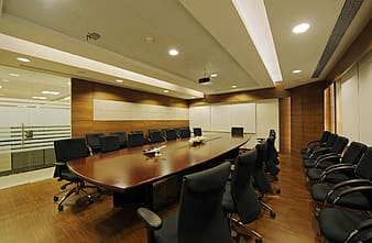 Brown wooden conference table between chairs