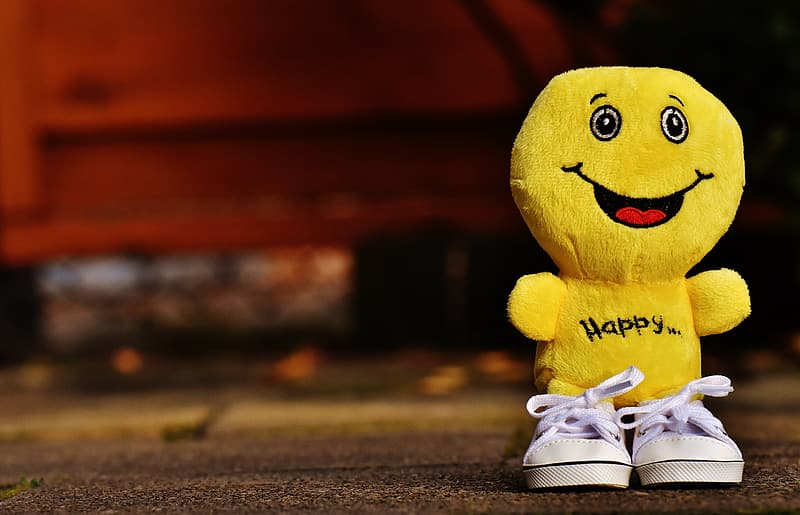 Purple happy plush toy wearing white sneakers