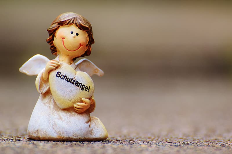 Closeup photography of white angel figurine carrying heart