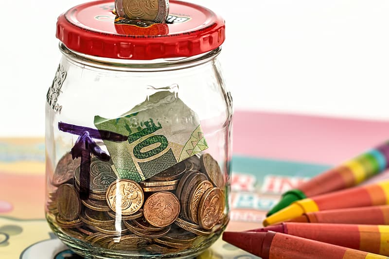Gold-colored coin in clear glass jar with 10 banknote near assorted-color crayons