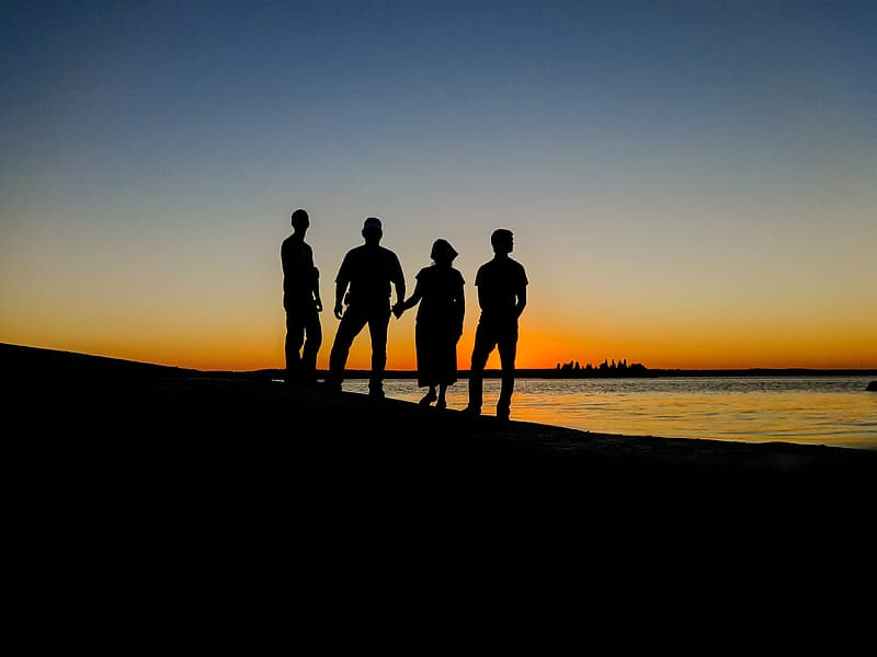Silhouette of four people standing during golden hour