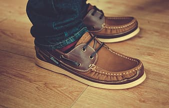 Person wearing black and brown leather shoe