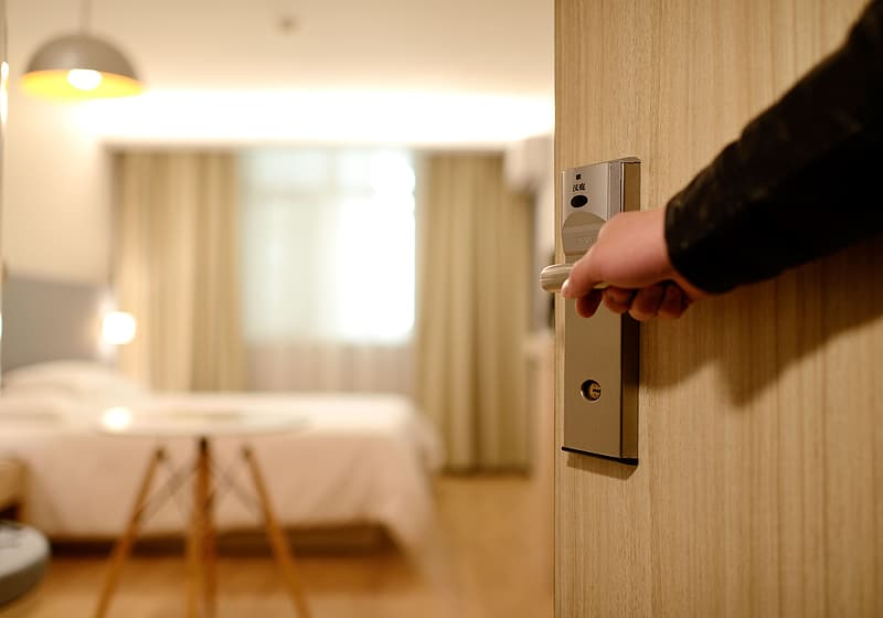 Person in black top opening a door to an empty room
