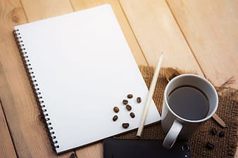 White ceramic mug beside white printer paper on brown wooden table