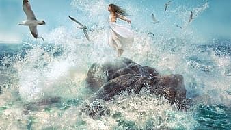 Flock of gulls flying over woman on rock near body of water