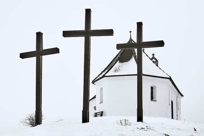 White and brown wooden church on snow covered ground