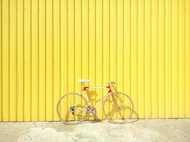 White and red road bike near yellow fence