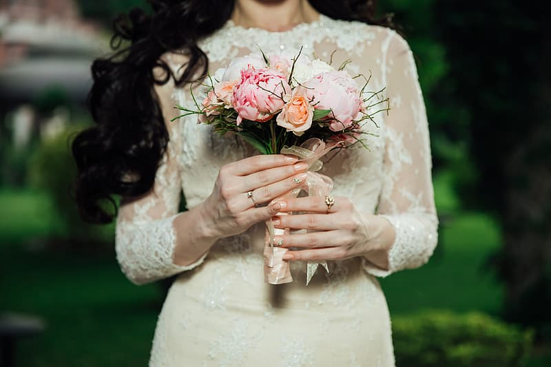 Woman standing while holding pink petaled flowers bouquet