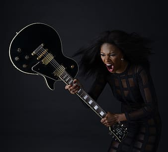 Woman in black and white stripe shirt playing electric guitar