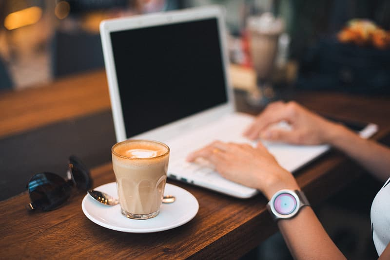 Person using macbook air beside white ceramic mug on brown wooden table