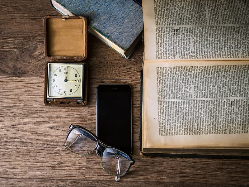 Black framed eyeglasses near black Android smartphone and book page