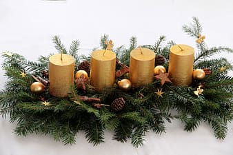Closeup photo of four pillar candles with green leaves