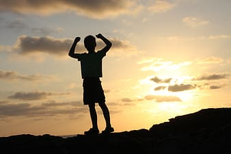Silhouette photo of boy on top of hill during daytime