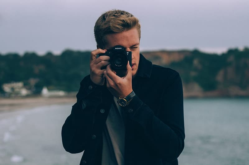 Man in black coat holding black dslr camera