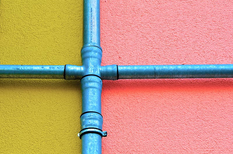Blue metal pipe on yellow and red concrete wall