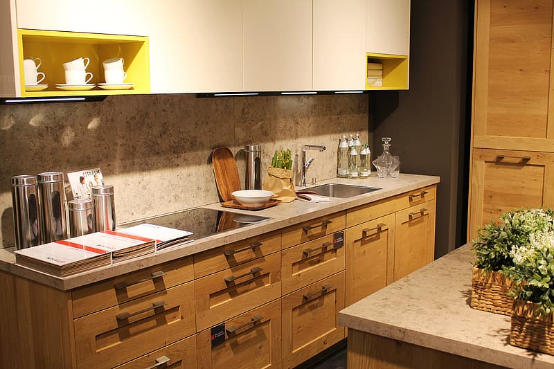 Photo of brown wooden kitchen cabinet with granite top and sink near white granite counter table