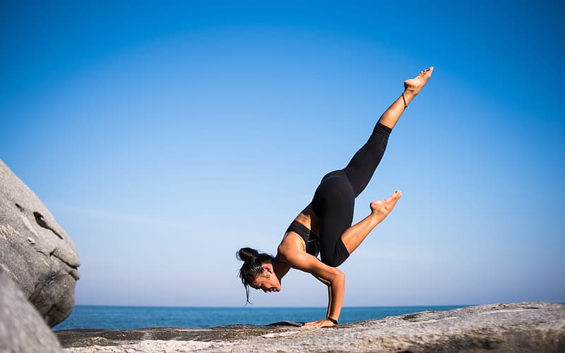 Woman in black tank top and black leggings doing yoga pose on beach during daytime