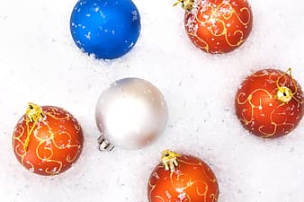 Blue and orange baubles on white snow