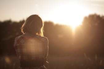 Woman in red and white checkered shirt standing during sun rise