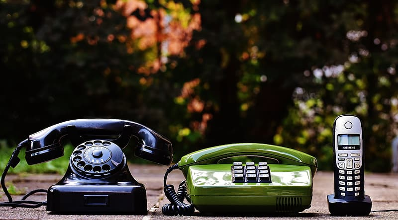Green rotary phone on black table