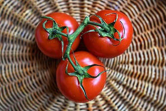 Three tomatoes on brown wicker basket