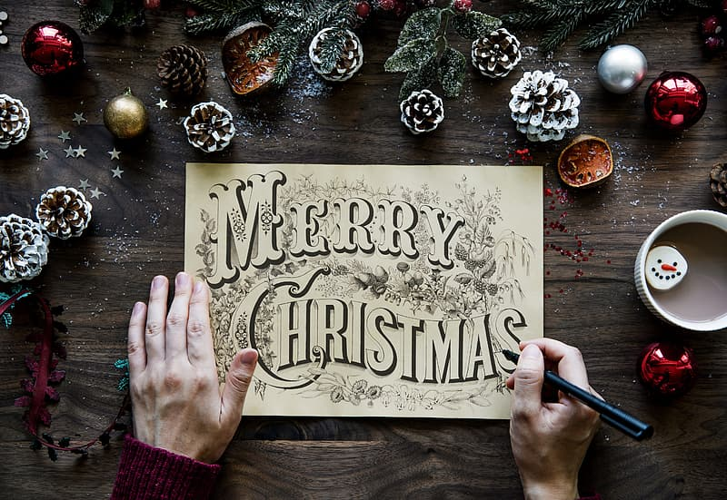 Person writing Merry Christmas on white paper