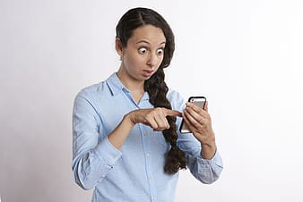 Woman wearing blue button-up collared long-sleeved shirt golding gold iPhone 5s with black bumper case