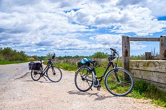 Black and gray bicycle on brown wooden fence under white clouds and blue sky during daytime