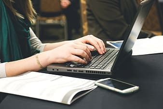 Woman typing on black laptop