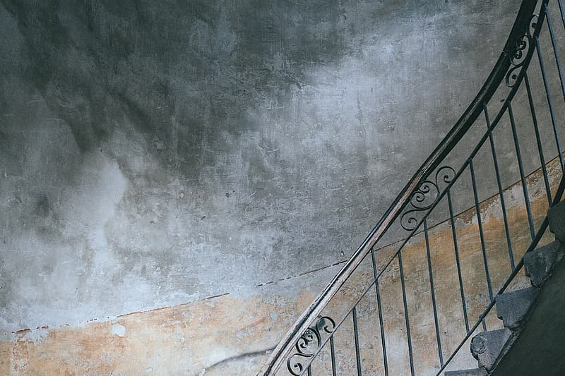 Black steel stair railings and gray concrete wall