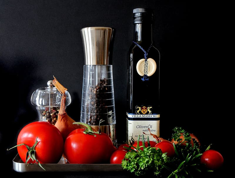 Black glass wine bottle with red tomatoes on stainless steel tray