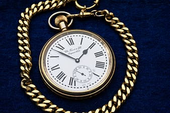 Round white analog pocket watch with gold-colored frame on blue textile