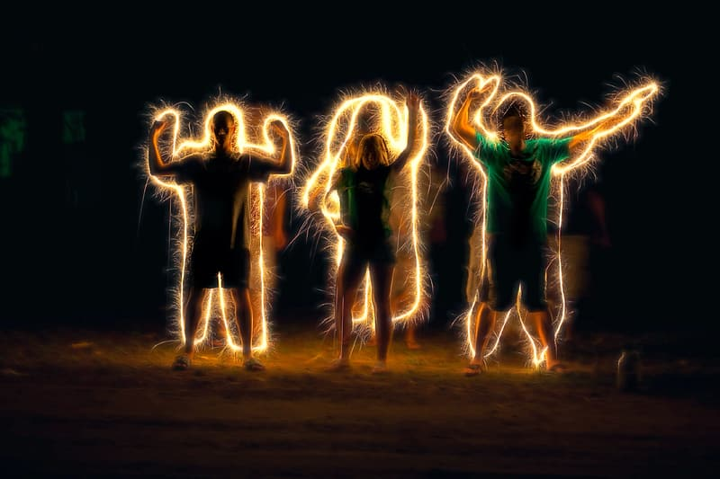 Steel wool photography of three persons standing