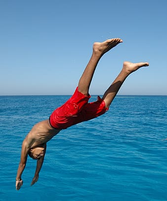Man about to dive at body of water