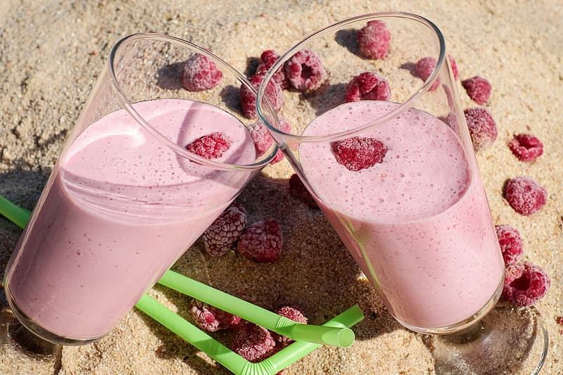 Two clear drinking glasses with rustberry shake