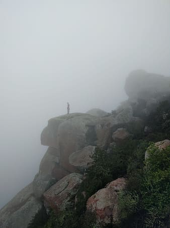 Person standing on rock formation during foggy day
