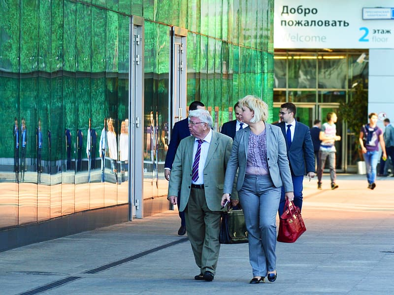 Man and woman walking near building with glass walls