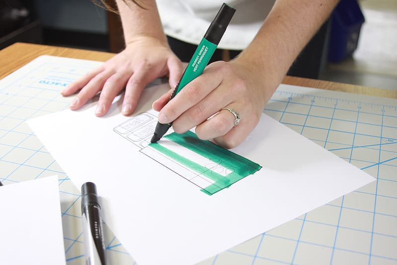 Person holding green and black pen