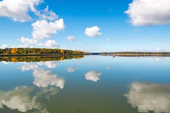 Body of water with clouds and sky reflection