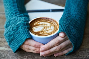 Woman wearing blue knitted long-sleeved shirt holding white ceramic teacup