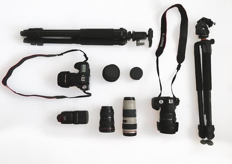 Flat-lay photography of two DSLR cameras and tripods
