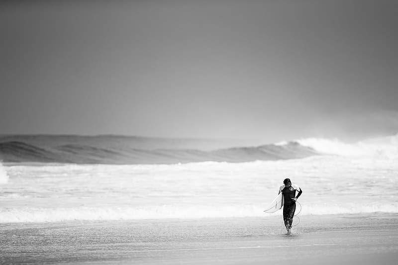 Gray scale photography of man holding surfboard on seashore