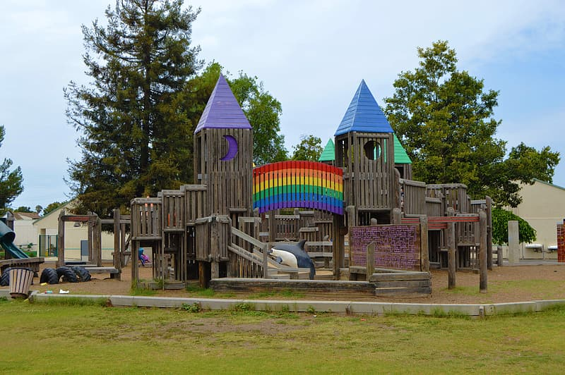Brown wooden playground park under white and blue sky during daytime