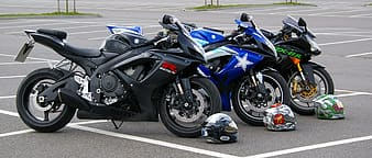 Two black and one blue sportbikes parked ahead