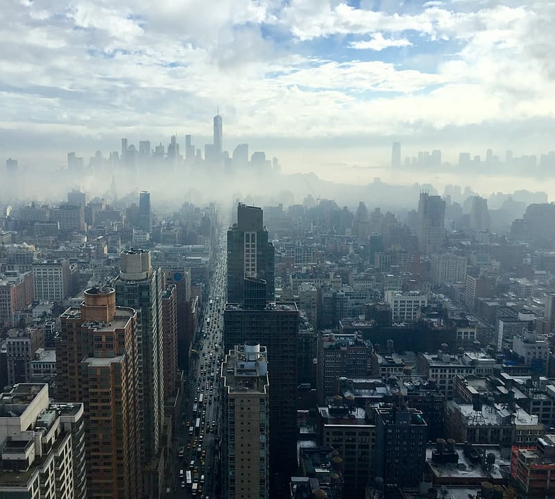 Aerial photo of high-rise and low-rise buildings surrounded by fogs