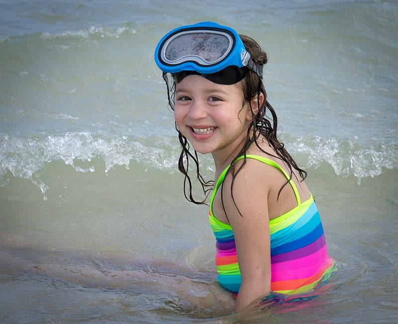 Girl wearing multicolored striped top and blue swimming goggles on body of watr
